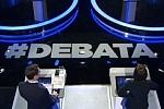 Fragment zdjęcia ze studia telewizyjnego z hashtagiem debata
